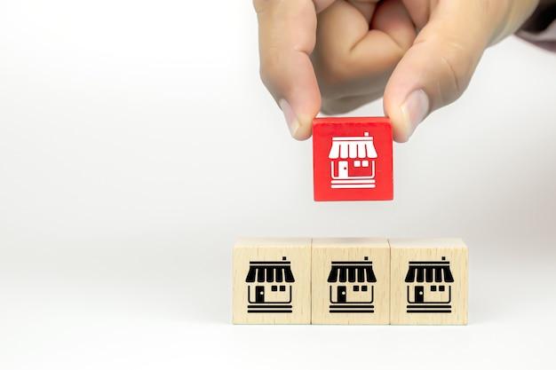 La mano del primo piano sta scegliendo i blocchi di legno del giocattolo del cubo impilati con l'icona del negozio di affari di franchising Foto Premium
