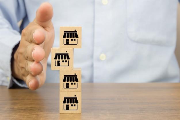 Mano del primo piano per proteggere i blocchi di legno del giocattolo del cubo impilati con l'icona del negozio di affari di franchising. Foto Premium