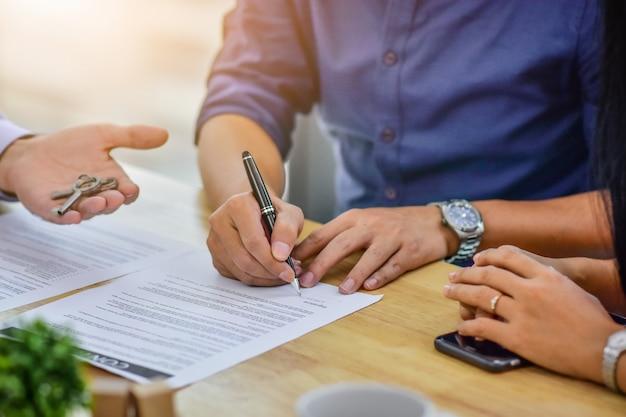 Chiuda sul contratto del segno della mano che compra a casa Foto Premium