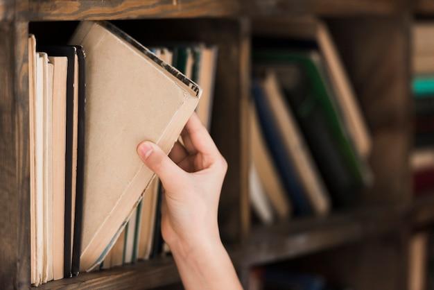 Mano del primo piano che prende il libro di storia dallo scaffale per libri Foto Premium