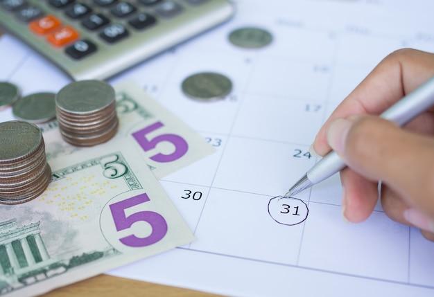 Chiudere la scrittura a mano sul calendario con la moneta Foto Premium