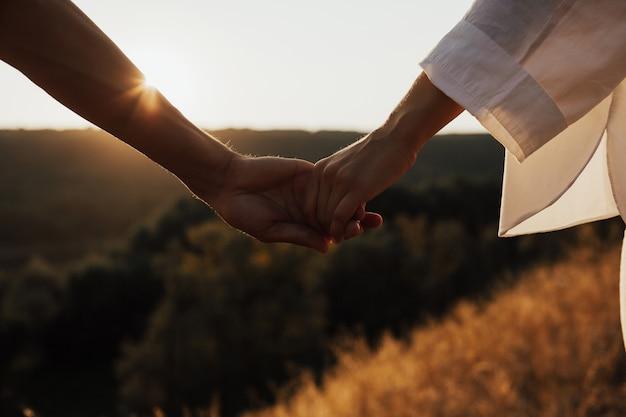 Primo piano delle mani della coppia. si tengono per mano al tramonto, sole. Foto Premium