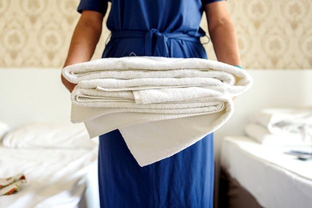 Primo piano delle mani che tengono una pila di asciugamani da bagno bianchi freschi. cliente in una stanza d'albergo. Foto Premium