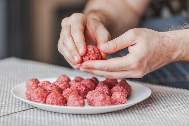 Primo piano sulle mani che preparano le polpette con carne tritata cruda Foto Premium