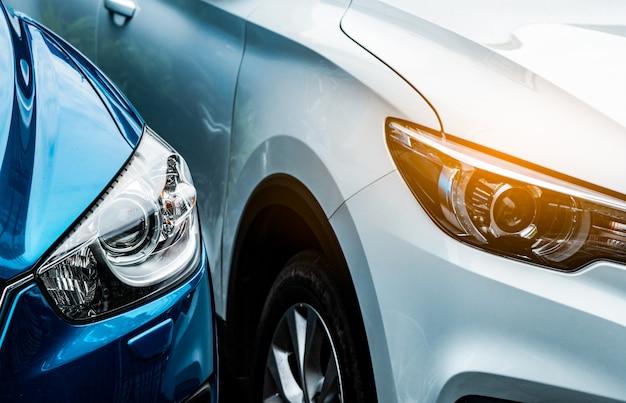 Chiuda sulla luce del faro dell'automobile suv blu e bianca. automobile blu parcheggiata accanto all'automobile bianca. concetto di industria automobilistica. concetto di auto elettrica o ibrida. servizio auto. avventura di viaggio. noleggio auto. Foto Premium