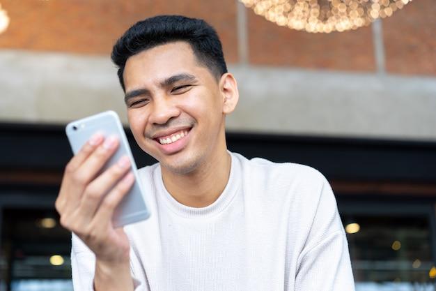 Chiuda sul gioco latino dell'uomo sul concetto dello smartphone Foto Premium