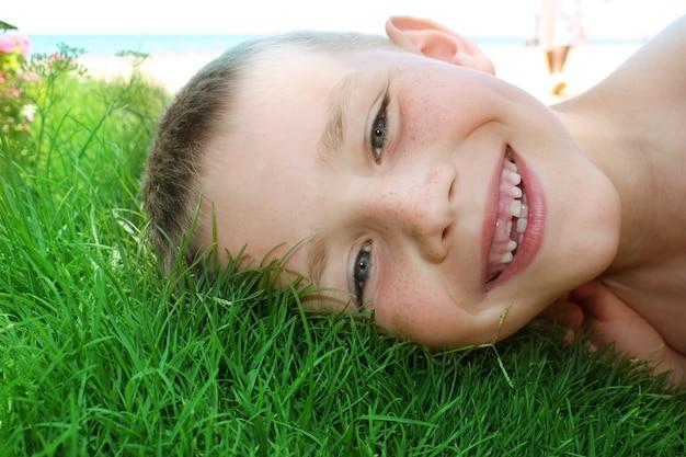 Primo piano sul ragazzino sorridente sull'erba Foto Premium