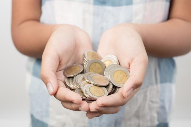 Primo piano delle mani della bambina che tengono le monete, il risparmio e il concetto bancario Foto Premium