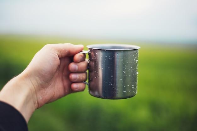 Primo piano della mano maschio che tiene la tazza d'acciaio spruzzata con acqua su priorità bassa di erba verde vaga. Foto Premium