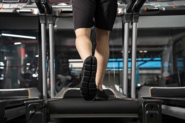 Chiuda in su delle gambe maschile in esecuzione sul tapis roulant in palestra Foto Premium