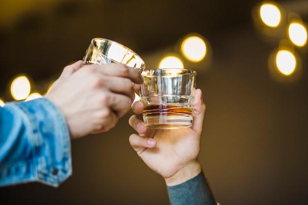 Primo piano della mano del maschio che tosta bicchiere di bevande contro il fondo del bokeh Foto Premium