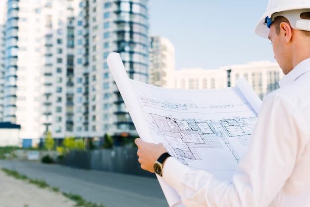 Uomo del primo piano che esamina progettazione di edifici Foto Premium