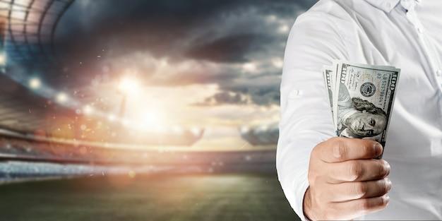 Primo piano della mano di un uomo che tiene i dollari usa sullo sfondo dello stadio. il concetto di scommesse sportive, realizzare un profitto dalle scommesse, dal gioco d'azzardo. football americano. Foto Premium