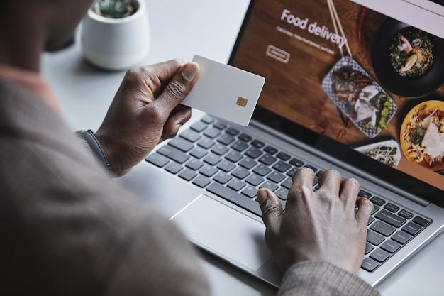 Primo piano dell'uomo seduto al tavolo davanti al computer portatile con carta di credito per ordinare cibo online Foto Premium