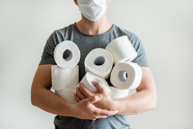 Chiuda sull'uomo con il fondo dei rotoli della carta igienica. concetto di mancanza di carta igienica nei negozi a causa di covid-19, coronavirus, igiene, panico. Foto Premium