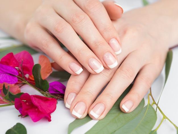 Chiuda sulle mani e sui fiori manicured Foto Premium