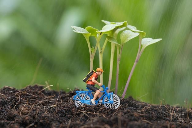 Primo piano del ciclista in miniatura con la crescita del germoglio di cavolo sul terreno e andare in bicicletta sotto la pioggia. Foto Premium