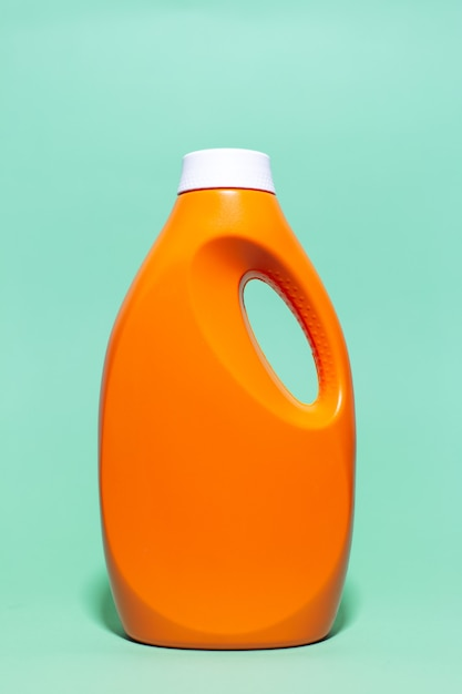 Close-up di arancione bottiglia di detersivo sulla parete di aqua menthe color. Foto Premium