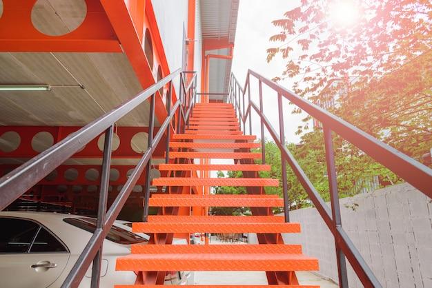 Chiuda in su della scala d'acciaio arancione o scala all'esterno dell'edificio. Foto Premium