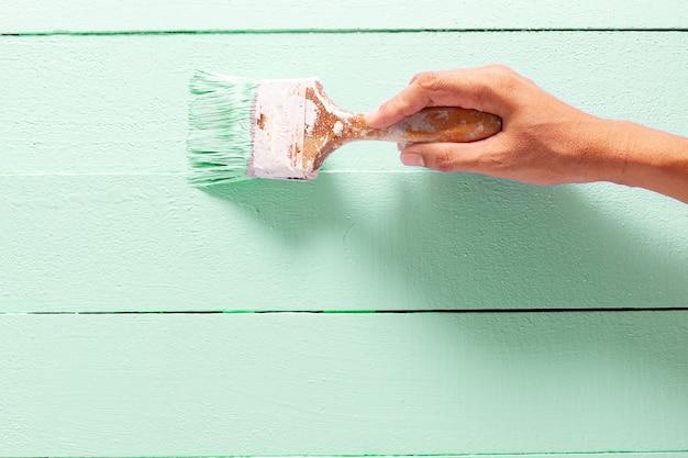 Chiuda sul colore verde della pittura della mano dell'uomo del pittore sul tavolo della plancia di legno con lo spazio della copia, interni luminosi di progettazione creativa e come dipingere la superficie di legno. Foto Premium