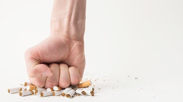 Primo piano della mano di una persona che rompe le sigarette con il suo pugno su sfondo bianco Foto Premium