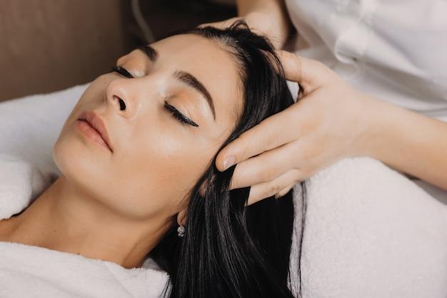Primo piano foto di una donna caucasica bruna sdraiata con gli occhi chiusi mentre si fa un massaggio alla testa presso il salone della stazione termale Foto Premium
