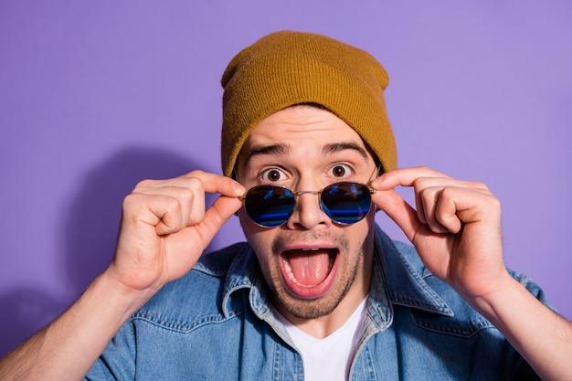 Close up foto di allegro eccitato divertente esultante ragazzo che indossa il cappuccio copricapo occhiali occhiali da vista gridando omg in denim isolato su sfondo di colore viola vivido Foto Premium