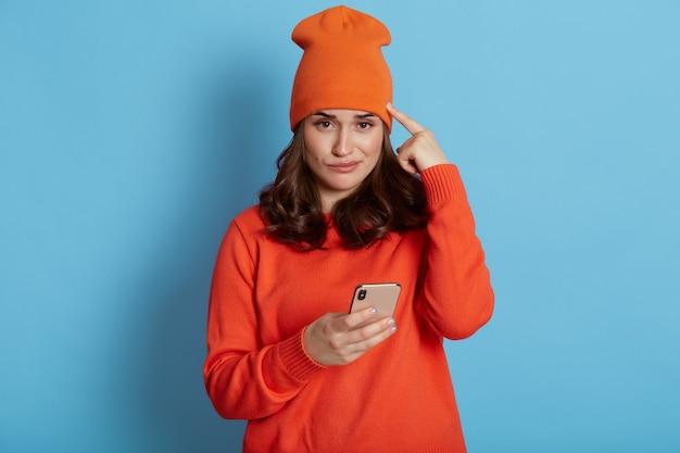 Chiuda sulla foto della splendida ragazza con i capelli scuri, leggendo qualcosa sul suo smartphone con l'espressione del viso perplesso e tenendo la testa con il dito indice, indossando berretto e maglione. Foto Premium