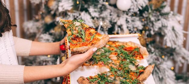 Close up foto della donna mano che tiene un trancio di pizza fresca su sfondo albero di natale Foto Premium