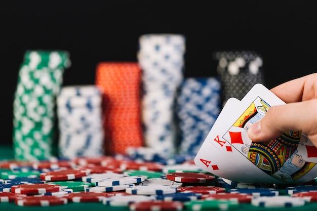Primo piano della mano di un giocatore che gioca a poker nel casinò Foto Premium