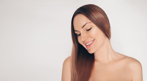Chiuda sul ritratto di bella donna mezza nuda naturale di bellezza con la pelle bianca perfetta isolata parete e dei capelli. pulizia del trattamento sanitario. concetto spa cura della pelle. Foto Premium