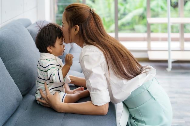 Chiuda sul ritratto di bella giovane madre asiatica che bacia il suo bambino appena nato per amare il concetto di giorno della madre di stile di vita della donna dell'asia con lo spazio della copia. Foto Premium