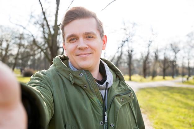 Chiuda sul ritratto di un uomo barbuto allegro che prende selfie sulla natura Foto Premium