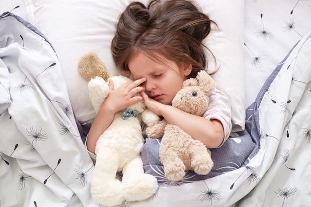 Chiuda sul ritratto di piccolo orsacchiotto caucasico sveglio della ragazza abbraccia il giocattolo molle dell'orsacchiotto e del cane. ritratto del bambino dolcemente addormentato con la tettarella Foto Premium