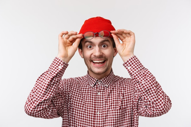 Ritratto di close-up di felice amichevole sorpreso ragazzo che toglie gli occhiali per dire ciao, sorridendo ampiamente vede una cosa fantastica, ha trovato il prodotto e lo ha raccolto, indossa un berretto rosso e una camicia a quadri, su un muro bianco Foto Premium