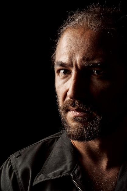 Chiuda sul ritratto di un uomo barbuto di mezza età pensieroso serio nel buio Foto Premium