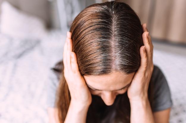 Close up ritratto di una giovane donna con ricresciuti capelli grigi radici radici. Foto Premium