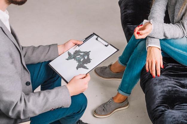Primo piano di uno psicologo che mostra il inkblot del rorschach sugli appunti al paziente Foto Premium