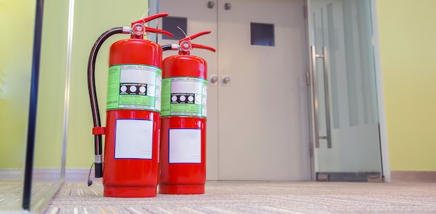 Primo piano il serbatoio rosso degli estintori alla porta di uscita dell'edificio. Foto Premium