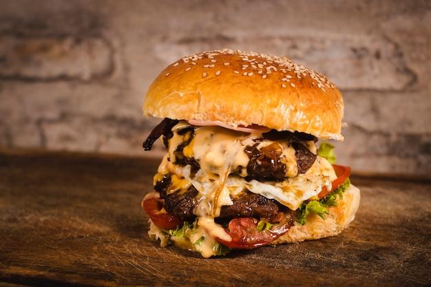 Immagine ravvicinata di un hamburguer gigante di bell'aspetto su una tavola di legno Foto Premium