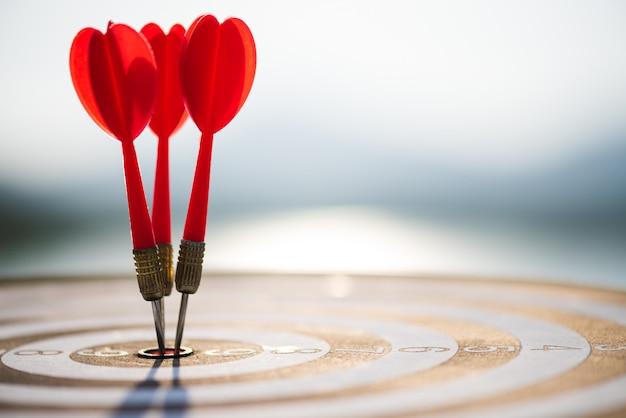 Chiuda sulle frecce rosse dei dardi del colpo nel centro dell'obiettivo. concetto di successo dell'obiettivo di affari. Foto Premium