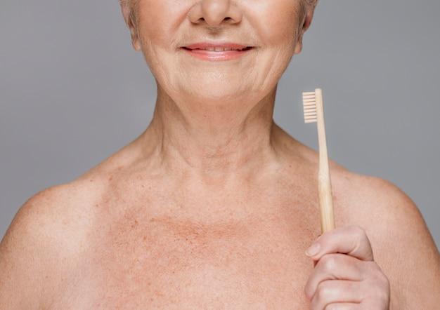 Close-up smiley donna azienda spazzolino da denti Foto Premium