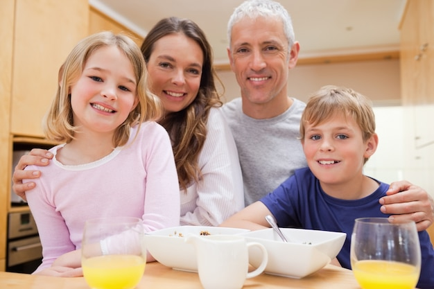 Chiuda in su di una famiglia sorridente facendo colazione Foto Premium