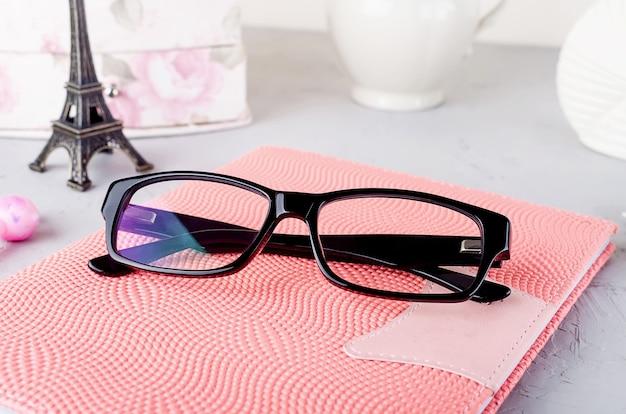 Close up occhiali da vista da donna alla moda nero sul taccuino rosa, Foto Premium