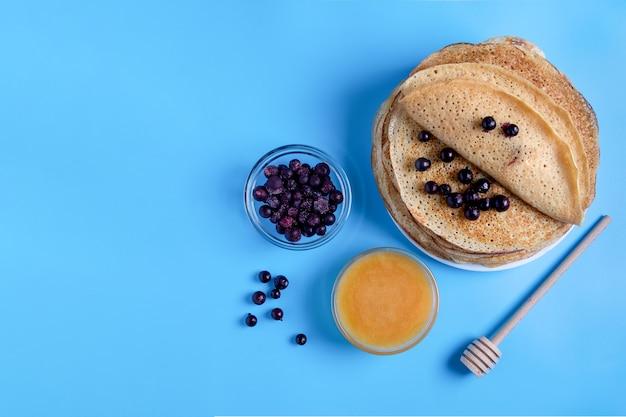 Primo piano vista dall'alto della cucina nazionale russa e frittelle dolci con frutti di bosco e miele. piatto tradizionale per shrovetide. messa a fuoco selettiva. copia spazio. Foto Premium