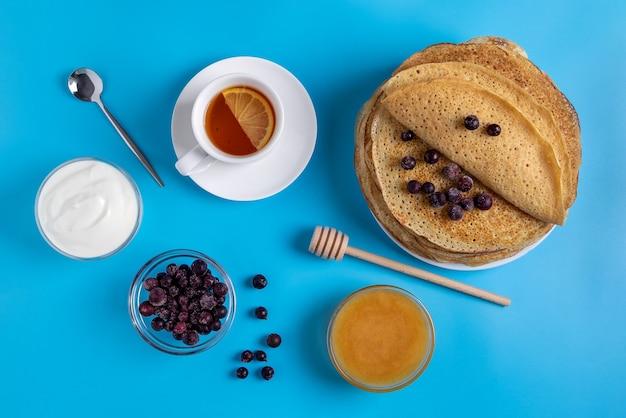 Primo piano vista dall'alto della cucina nazionale russa e frittelle dolci con panna acida, frutti di bosco e miele. piatto tradizionale per shrovetide. messa a fuoco selettiva. Foto Premium