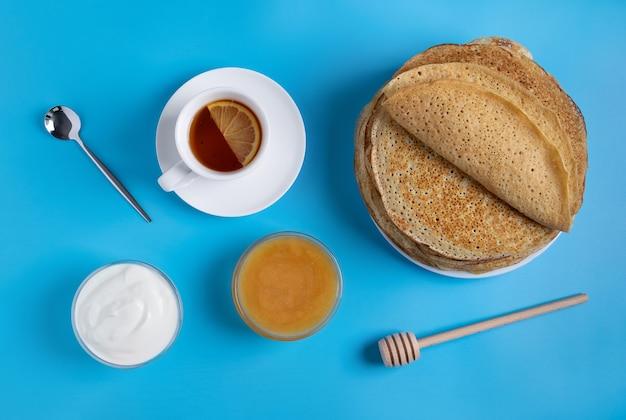 Primo piano vista dall'alto della cucina nazionale russa e frittelle dolci con panna acida e miele. piatto tradizionale per shrovetide. messa a fuoco selettiva. Foto Premium
