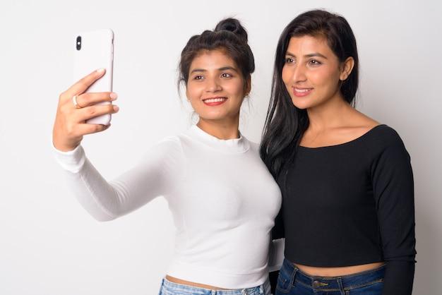 Primo piano di due giovani belle donne persiane insieme come sorelle isolate Foto Premium