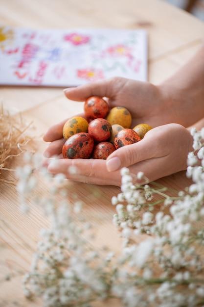 Primo piano di donna irriconoscibile che tiene piccole uova colorate mentre si prepara per le vacanze di pasqua Foto Premium