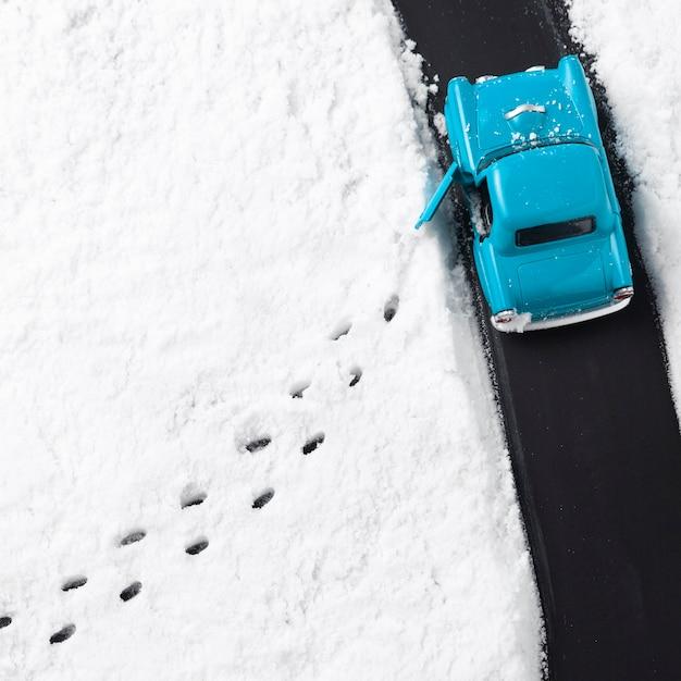 Vista ravvicinata della macchinina blu con la neve Foto Premium